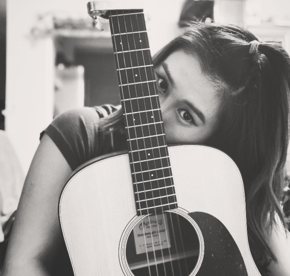 A girl holding her guitar and smiling.